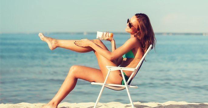 model applying sunscreen to legs