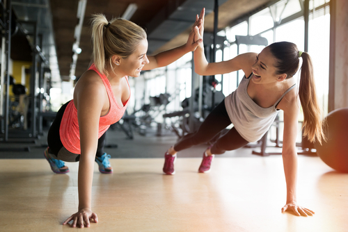 2 female models high fiving while exercising